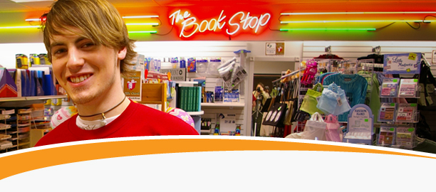 Male college student in red tee shirt smiling at camera in front merchandise at the Book Stop.