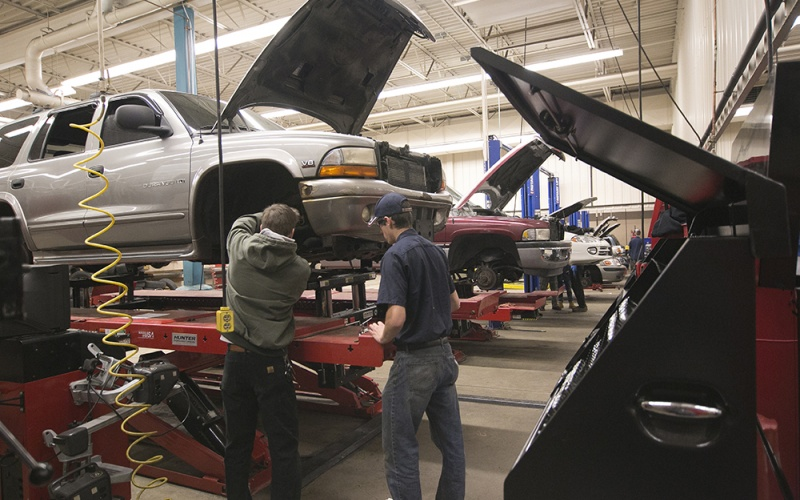 Students working on a car on a lift