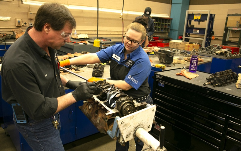 Student and instructor working on an engine
