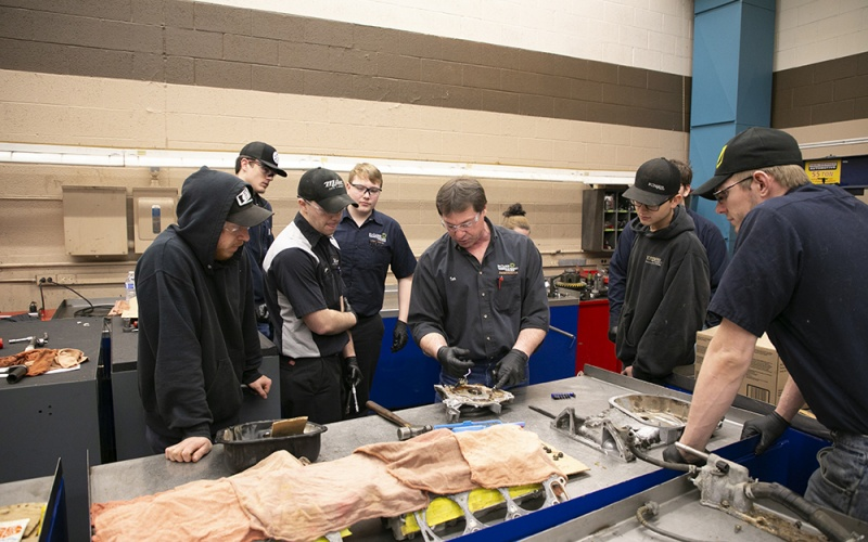Students watching an instructor in the auto lab