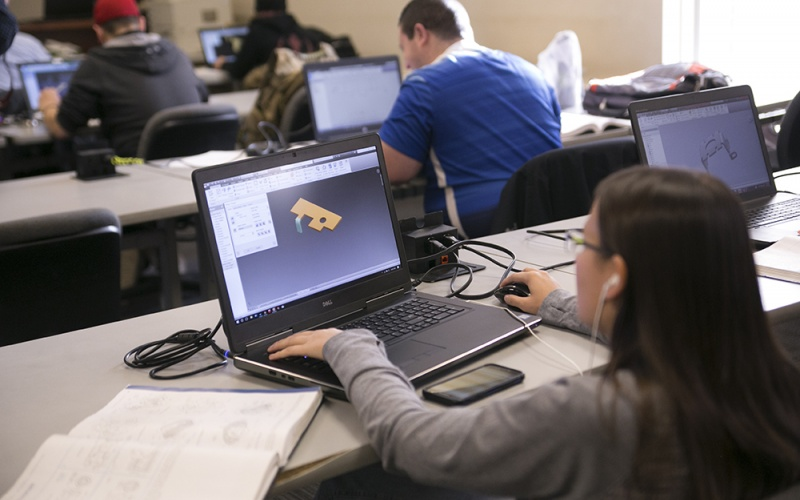 Student at laptop with design on the screen and students in the background