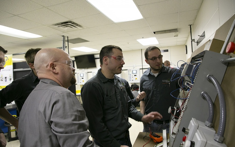 Students looking at a control panel