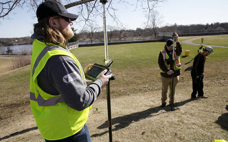 Students outside with surveying equipment