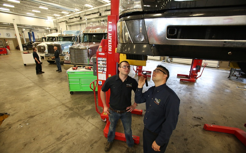 Student and instructor standing under a truck on a lift