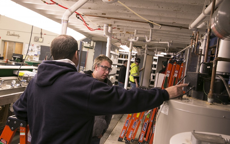 A student and the instructor in the plumbing lab