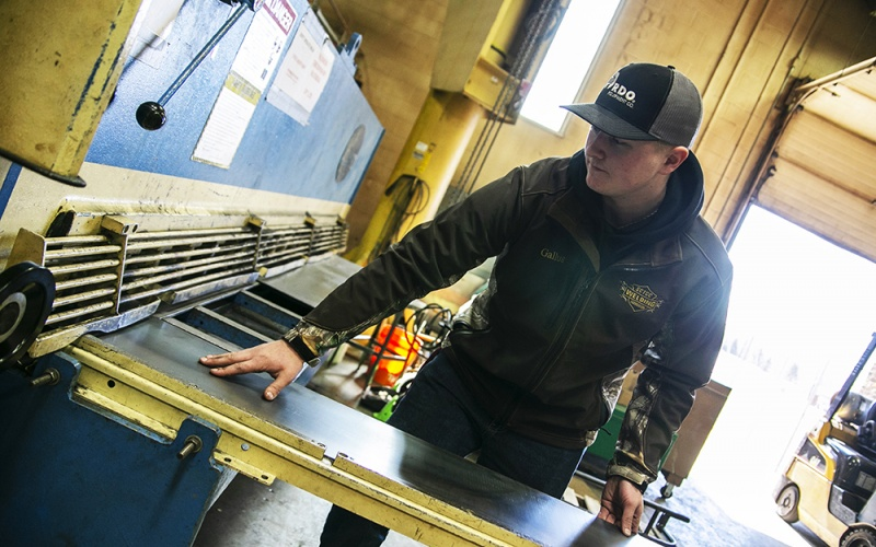 Student feeding metal to a large welding machine