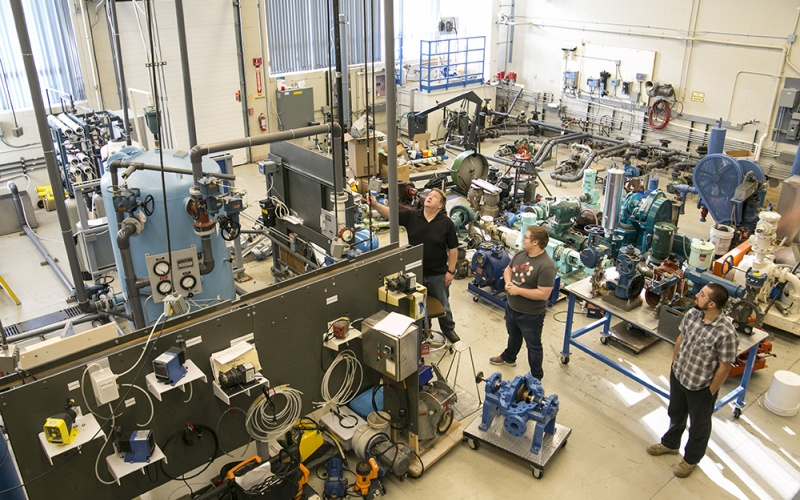 Students and instructor looking at large equipment