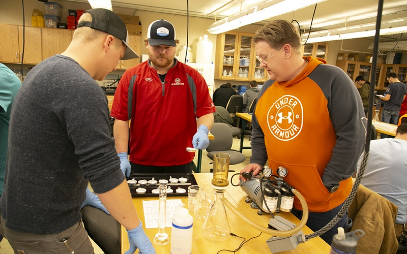 Students and instructor working at a table with water in tubes