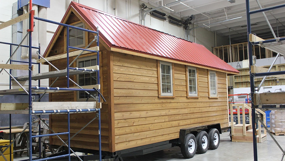 A small, wooden home on wheels. Made by carpentry students at SCTCC