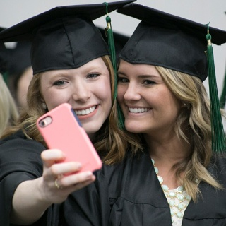 Two girls take a selfie in their SCTCC graduation caps and gowns