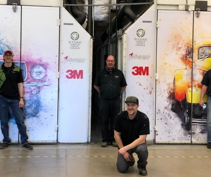 Paint booths in auto body with instructors standing in front