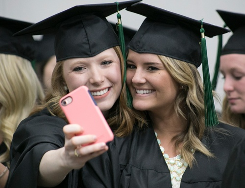 5d058ce8c12 Two girls take a selfie in their SCTCC graduation caps and gowns