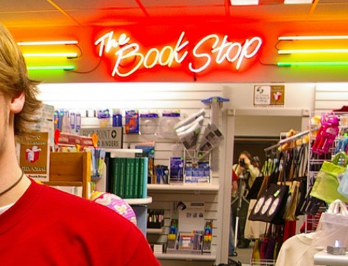 """Young male student poses in front of a big neon sign that reads """"The Bookstop"""""""