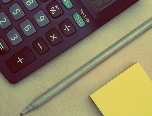 Calculator, pen and yellow sticky notes